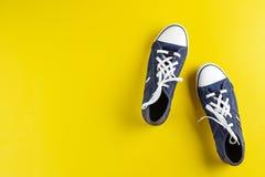 Zapatillas de deporte en un fondo amarillo imagenes de archivo