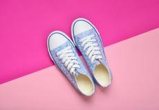 Zapatillas de deporte femeninas clásicas con los cordones blancos de 80s en un fondo en colores pastel rosado Imágenes de archivo libres de regalías