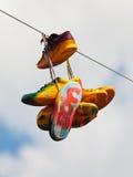 Zapatillas de deporte gastadas con la pintada que cuelga en una cuerda Imagenes de archivo