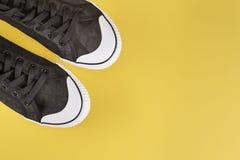 Zapatillas de deporte negras en un fondo amarillo Fotografía de archivo libre de regalías