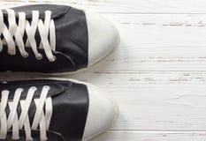 Zapatillas de deporte para hombre de cuero en fondo de madera del vintage blanco Copie s Foto de archivo libre de regalías