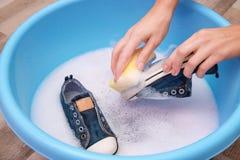 Zapatillas de deporte que se lavan de la mujer con la esponja sobre el lavabo plástico, fotografía de archivo