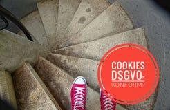 Zapatillas de deporte rojas en escalera espiral al ir cuesta abajo con la inscripción en las galletas alemanas DSGVO-konform en l Imagen de archivo
