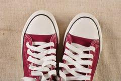 Zapatillas de deporte rojas en fondo retro de la tela vieja Foto de archivo libre de regalías