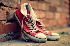 Zapatillas de deporte rojas que se inclinan contra una pared de ladrillo con efecto retro Imagen de archivo libre de regalías