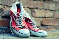 Zapatillas de deporte rojas que se inclinan contra una pared de ladrillo con efecto retro Fotografía de archivo libre de regalías