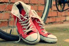 Zapatillas de deporte rojas que se inclinan en una bici vieja Imágenes de archivo libres de regalías