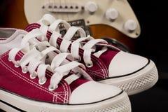 Zapatillas de deporte rojas y guitarra borrosa en fondo Fotografía de archivo libre de regalías