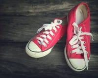 Zapatillas de deporte rosadas de la señora joven en piso de madera Tono del vintage Fotos de archivo libres de regalías