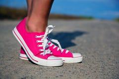 Zapatillas de deporte rosadas en las piernas de la muchacha Foto de archivo libre de regalías
