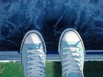 Zapatillas de deporte sobre el mar Imágenes de archivo libres de regalías