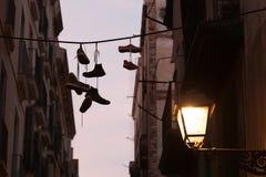 Zapatillas de deporte sucias que cuelgan en la silueta de la cuerda para tender la ropa foto de archivo libre de regalías
