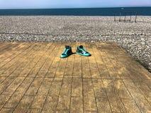 Zapatillas de deporte verdes de los deportes, zapatos en una plataforma de madera en una playa arenosa contra la perspectiva del  imagen de archivo