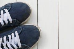 Zapatillas de deporte viejas en el fondo de madera blanco del piso Imágenes de archivo libres de regalías