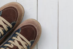 Zapatillas de deporte viejas en el fondo de madera blanco del piso Imagenes de archivo