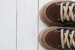 Zapatillas de deporte viejas en el fondo de madera blanco del piso Fotografía de archivo libre de regalías