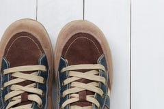 Zapatillas de deporte viejas en el fondo de madera blanco del piso Imagen de archivo