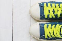 Zapatillas de deporte viejas en el fondo de madera blanco del piso Imagen de archivo libre de regalías