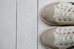 Zapatillas de deporte viejas en el fondo de madera blanco del piso Fotografía de archivo