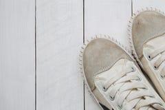 Zapatillas de deporte viejas en el fondo de madera blanco del piso Foto de archivo libre de regalías