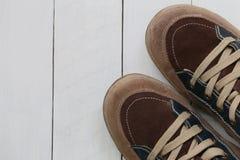 Zapatillas de deporte viejas en el fondo de madera blanco del piso Foto de archivo