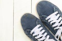 Zapatillas de deporte viejas en el fondo de madera blanco del piso Fotos de archivo libres de regalías