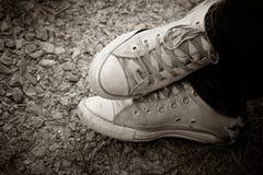 Zapatillas de deporte viejas en el piso Fotografía de archivo libre de regalías