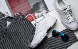 Zapatillas de deporte y accesorios del cuero blanco en un fondo blanco Fotografía de archivo