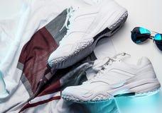 Zapatillas de deporte y accesorios del cuero blanco en un fondo blanco Imagenes de archivo