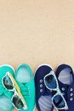 Zapatillas de deporte y gafas de sol verdes y azules en fondo marrón Fotos de archivo