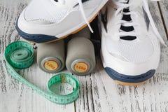 Zapatillas de deporte y pares de pesas de gimnasia en fondo de madera Pesos para Foto de archivo