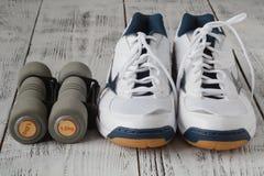 Zapatillas de deporte y pares de pesas de gimnasia en fondo de madera Pesos para Fotografía de archivo