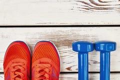 Zapatillas de deporte y pesas de gimnasia de la mujer Imagenes de archivo