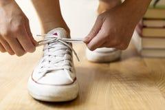 Zapatillas de deporte y pila blancas de libros en el piso Estudiante, educati Fotografía de archivo libre de regalías