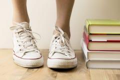 Zapatillas de deporte y pila blancas de libros en el piso Estudiante, educati Imagen de archivo