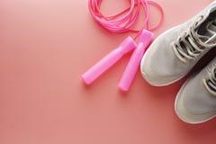 Zapatillas de deporte, zapatos del deporte y cuerda de salto sobre fondo rosado Salud, concepto de funcionamiento del entrenamien fotos de archivo
