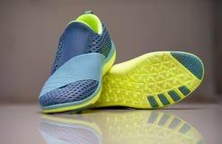 Zapatillas deportivas de la mujer sin la secuencia en fondo de la falta de definición con el refle foto de archivo