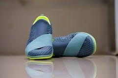 Zapatillas deportivas de la mujer sin la secuencia en fondo de la falta de definición con el refle imagen de archivo