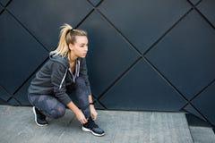 Zapatillas deportivas que intentan de la mujer del atleta que consiguen listas para activar al aire libre en la ciudad fotos de archivo libres de regalías