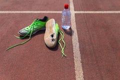 Zapatillas deportivas verdes quebradas con la botella de agua imagen de archivo libre de regalías