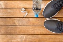 Zapatillas deportivas y accesorios grises de los deportes en fondo de madera fotos de archivo libres de regalías