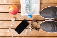 Zapatillas deportivas y accesorios grises de los deportes en fondo de madera fotos de archivo