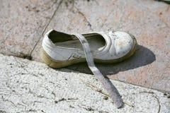 Zapato blanco de los niños perdidos en la calle Imagenes de archivo