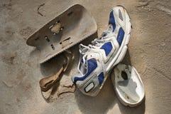 Zapato dañado del deporte y viejos protectores de la rodilla Imagenes de archivo