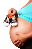Zapato de bebé de la explotación agrícola de la mujer embarazada foto de archivo libre de regalías