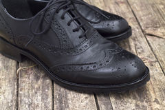 Zapato de cuero con el cordón en fondo de madera fotos de archivo