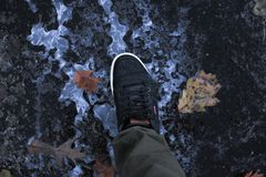 Zapato de Levis que camina en el asfalto mezclado con hielo fotos de archivo libres de regalías