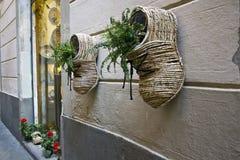 Zapato de mimbre con las flores en una pared Foto de archivo