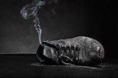 Zapato de trabajo viejo en humo Fotos de archivo