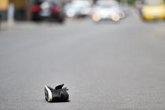 Zapato en la calle con los coches en fondo después del accidente Fotografía de archivo libre de regalías